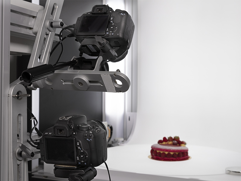zoom on two cameras fixed on the multi arm to shoot a cake with multiple angles